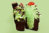A chocolate cupcake decorated with mint cream, chocolate sauce and a cherry (Christmas)