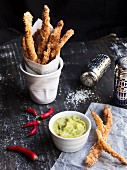 Baked chicken sticks in a cup with guacamole on a black wooden table
