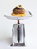 Cheeseburger mit Champignons auf mechanischer Küchenwaage