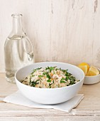 Lemon and rocket risotto with a carafe of water bottle and lemon wedges