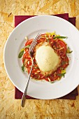 Turkey escalope with a mozzarella coating on a bed of tomato carpaccio