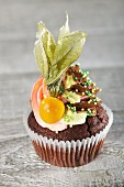 A chocolate cupcake with buttercream, sugar sprinkels and a physalis