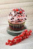 A chocolate cupcake decorated with strawberry cream, chocolate pearls and redcurrants