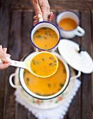 Sweet potato soup with ginger being ladled into an enamel mug