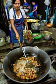 An oriental woman cooking pork in a large wok (Klong Toey Market, Bangkok, Thailand)
