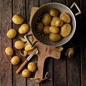 An arrangement of potatoes featuring peeled potatoes and potato peelings