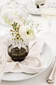 Spring flowers in drinking glass on set table