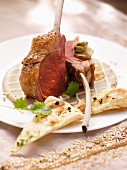 Rack of lamb on a spicy aubergine sauce with coconut yogurt