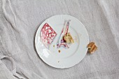 Mortadella slices, bacon slices and a piece of baguette on a white porcelain plate