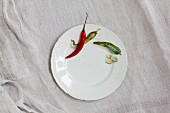 Chilli peppers and slices of cucumber on a white porcelain plate
