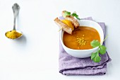 Curry soup with a chicken skewer and fresh coriander