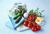 A board and a napkin with tomatoes, eggs, cucumbers and herbs and a jar of gherkins on a blue and white checked tablecloth