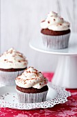 Three Red Velvet cupcakes on a plate and on a cake stand