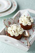 Two chocolate and coconut cupcakes on a floral napkin