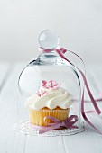 A cupcake decorated with pink sugar flowers under a glass cloche