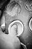 Mürbteig mit der Hand in Muffinform drücken (s/w-Aufnahme)