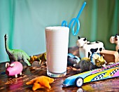A vanilla milkshake on a wooden table surrounded by toys