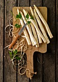 Peeled white asparagus on chopping board
