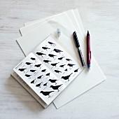 Zeichenstifte neben Buch mit verschiedenen Abbildungen von Vögeln