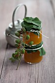Two jars of greengage jam with the lids tied with blackberry leaves