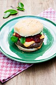 Grilled cheeseburger with tomatoes and basil on a green plate