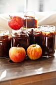 Mehrere Gläser hausgemachtes Apfelchutney und frische Äpfel