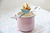 A mini cupcake balanced on a spoon over a pink enamel mug