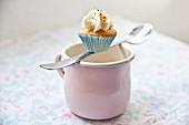 A mini cupcake balanced on a spoon over a pink enamel mug