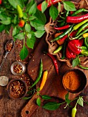 Various chilli peppers, chilli flakes and powder on a wooden board
