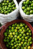 Limes in two sacks and a plastic container
