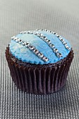 A chocolate cupcake decorated with silver pearls