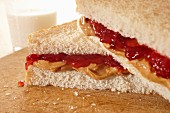A peanut butter and jam sandwich with a glass of milk