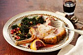A pork chop with pomegranate seeds, green kale and blood oranges