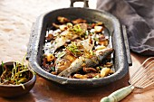 Roasted sardines with vegetables and herbs in an iron pan
