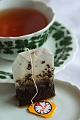A teabag in front of a tea cup