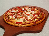 A pizza topped with pepperoni, pepper and mozzarella on a chopping board