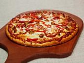 Pizza mit Peperoniwurst, Paprika und Mozzarella auf Schneidebrett