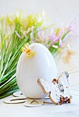 A white egg decorated with butterflies in front of spring flowers