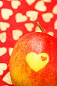 A heart carved into a red apple (detail)