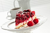 A slice of raspberry cake on a cake stand and with a coffee pot and a cup of coffee in the background
