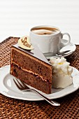 A slice of Sachertorte (rich Austrian chocolate cake) with cream served with a cup of coffee