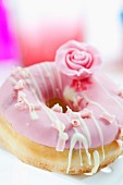 A doughnut topped with pink icing and a sugar rose