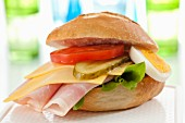 A bread roll filled with ham, cheese, tomatoes, egg and gherkins on a chopping board