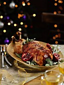 Roast turkey wrapped in bacon on sage with pomegranate seeds