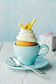 A banana and honey cupcake in a blue cup with a tea spoon and a gift in the background