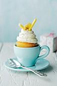 Bananen-Honig-Cupcake in blauer Tasse mit Teelöffel und Geschenk