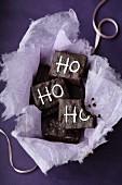 Mehrere Brownies mit Ho, Ho, Ho Zuckerschrift auf lila Untergrund