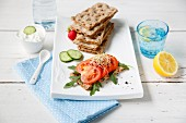 Crisp bread with a dip, tomatoes, cucumber, rocket and lemon water
