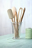 Various wooden kitchen utensils in a measuring jug next to a roll of green kitchen twine