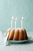 Lemon cake with icing sugar and three burning candles